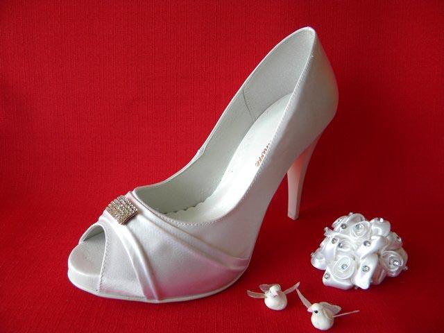 Lodičková obuv na platformě má výšku podpatku 10 cm. Svršek je vyroben ze  saténu bílé nebo smetanové. barvy a je ozdoben stříbrnou broží. 81429f351b